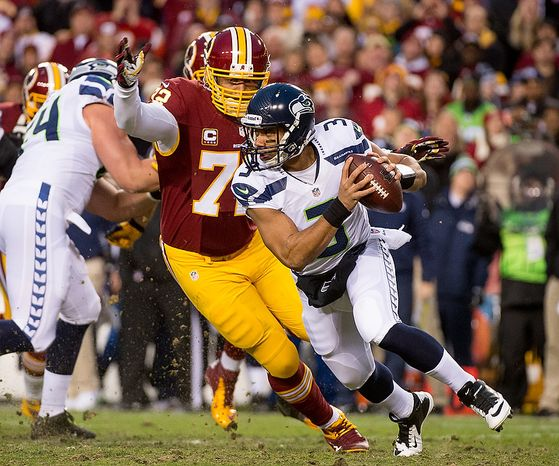 Seattle Seahawks quarterback Russell Wilson (3) scrabbles before being sacked by Washington Redskins defensive end Stephen Bowen (72), center, and Washington Redskins inside linebacker London Fletcher (59) in the first quarter as the Washington