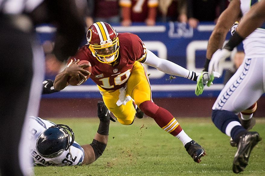 Washington Redskins quarterback Robert Griffin III (10) is pushed out of bounds after scrabbling in the first quarter as the Washington Redskins play the Seattle Seahawks during the NFC wild card game at FedEx Field, Landover, Md., Sunday, January 6, 2013. (Andrew Harnik/The Washington Times)