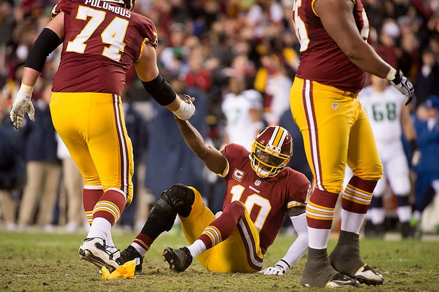 Washington Redskins tackle Tyler Polumbus (74) helps up Washington Redskins quarterback Robert Griffin III (10) after being illegally hit while throwing a 4 yard touchdown as the Washington Redskins play the Seattle Seahawks during the NFC wild card game at FedEx Field, Landover, Md., Sunday, January 6, 2013. (Andrew Harnik/The Washington Times)