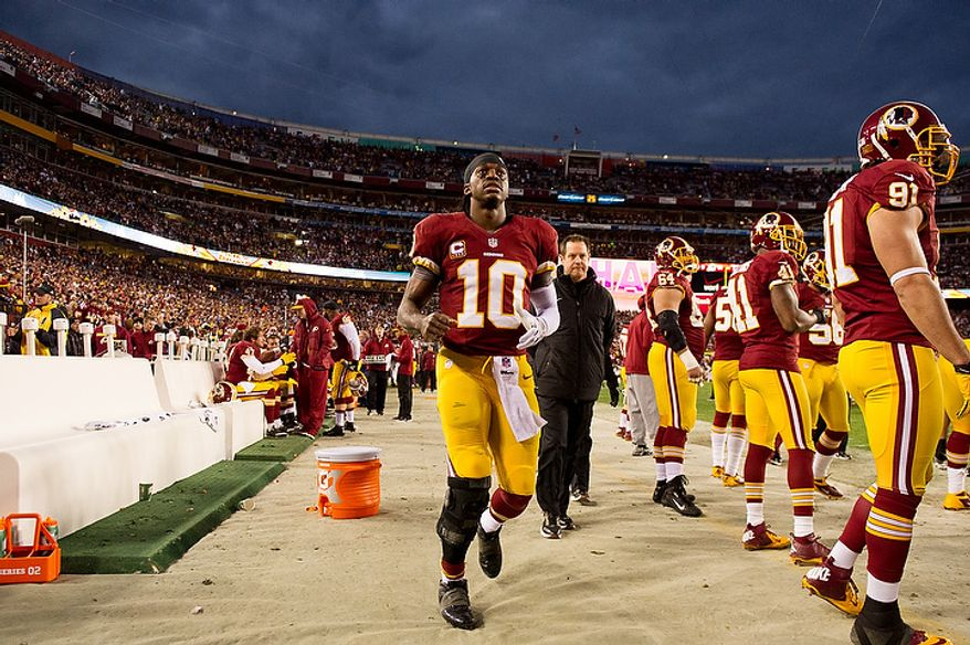 Washington Redskins quarterback Robert Griffin III (10) tests out his injured knee on the sideline after being hit after a touchdown pass in the first quarter as the Washington Redskins play the Seattle Seahawks during the NFC wild card game at FedEx Field, Landover, Md., Sunday, January 6, 2013. (Andrew Harnik/The Washington Times)