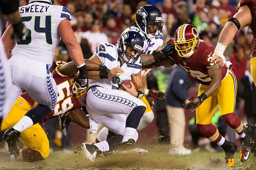 Seattle Seahawks quarterback Russell Wilson (3) is tackled by Washington Redskins inside linebacker London Fletcher (59) after a 19 yard scramble as the Washington Redskins play the Seattle Seahawks during the NFC wild card game at FedEx Field, Landover, Md., Sunday, January 6, 2013. (Andrew Harnik/The Washington Times)