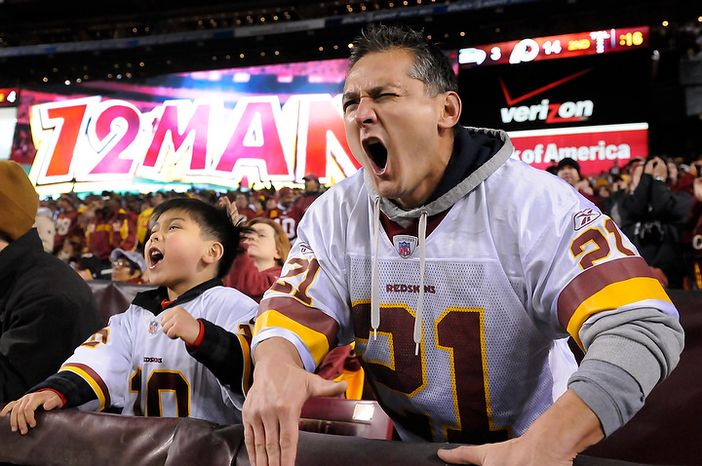 Auguste Remy and his son Dillon, 6, from Gaithersburg, Md., scream while the Redskins are on defense in the NFC wild card game at FedEx Field, Landover, Md., Jan. 6, 2013. (Preston Keres/Special to The Washington Times)