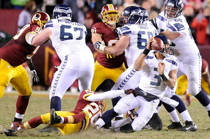 Seattle Seahawks quarterback Russell Wilson (3) is sacked by Washington Redskins cornerback Josh Wilson (26) in the third quarter of the NFC wild card game at FedEx Field, Landover, Md., Jan. 6, 2013. (Preston Keres/Special to The Washington Times)