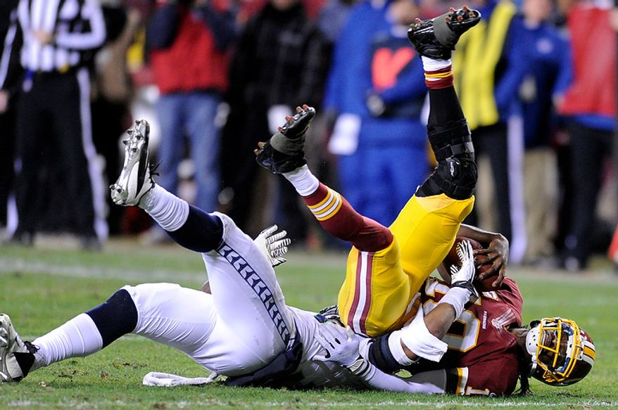 Washington Redskins quarterback Robert Griffin III (10) is sacked by Seattle Seahawks defensive end Bruce Irvin (51) for a loss of 12 yards in the fourth quarter of the NFC wild card game at FedEx Field, Landover, Md., Jan. 6, 2013. (Preston Keres/Special to The Washington Times)