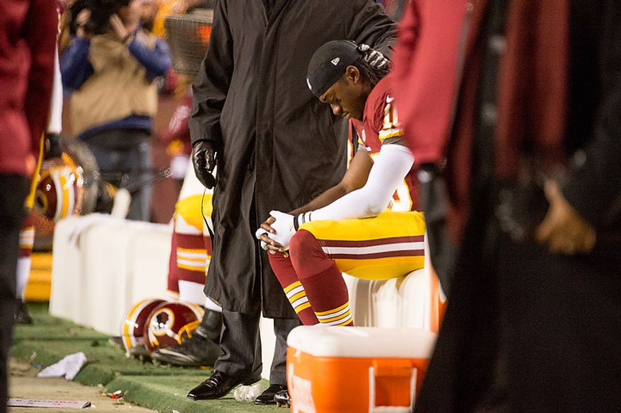 Washington Redskins quarterback Robert Griffin III (10) sits on the sideline after leaving the game with an injured knee late in the fourth quarter as the Washington Redskins play the Seattle Seahawks during the NFC wild card game at FedEx Field, Landover, Md., Sunday, January 6, 2013. (Andrew Harnik/The Washington Times)