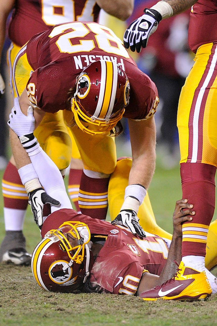 Washington Redskins tight end Logan Paulsen (82) bends over to help quarterback Robert Griffin III (10) after being injured in the fourth quarter of the NFC wild card game at FedEx Field, Landover, Md., Jan. 6, 2013. (Preston Keres/Special to The Washington Times)