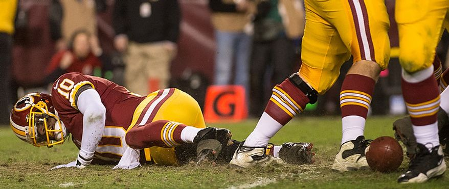 Washington Redskins quarterback Robert Griffin III (10) injures his knee on a bad snap which was recovered by the Seattle Seahawks late in the fourth quarter as the Washington Redskins play the Seattle Seahawks during the NFC wild card game at FedEx Field, Landover, Md., Sunday, January 6, 2013. (Andrew Harnik/The Washington Times)