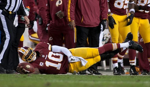 Washington Redskins quarterback Robert Griffin III (10) dives for a first down in the first half against the Seattle Seahawks in the NFC wild card game at FedEx Field, Landover, Md., Sunday, January 6, 2013. (Craig Bisacre/The Washington Times)