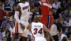 Washington Wizards' Kevin Seraphin (13) shoots against Miami Heat's LeBron James (6) and Ray Allen (34) during the first half of an NBA basketball game in Miami, Sunday, Jan. 6, 2013. (AP Photo/Alan Diaz)