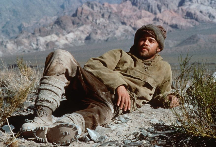 """Actor Brad Pitt, who portrayed Austrian mountaineer and former Nazi Party member Heinrich Harrer in the film """"Seven Years in Tibet,"""" reclines on a mountain ledge during the filming of the movie. (AP Photo/David Appleby"""