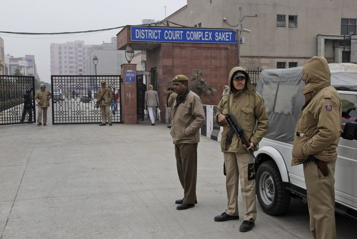 Indian police officers stand outside the district court where five men accused in a gang rape were brought to appear in New Delhi on Monday, Jan. 7, 2013. (AP Photo/Manish Swarup)