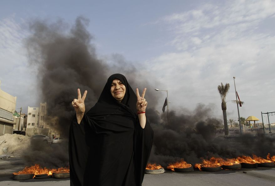 A Bahraini anti-government protester poses for a photograph flashing the victory sign in front of burning tires on a road in the village of Dumistan, Bahrain, on Monday, Jan. 7, 2013. The country's highest court has upheld jail sentences against 20 opposition figures convicted of plotting to overthrow the Western-allied government, including eight prominent activists facing life in prison. The ruling is almost certain to bring strong criticism from rights groups and touch off more street protests in the violence-wracked Gulf kingdom. (AP Photo/Hasan Jamali)