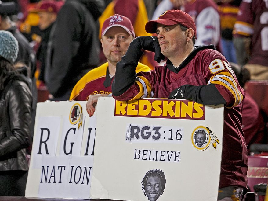 Holding signs showing their support of Redskins quarterback Robert Griffin III, two fans stand stunned Sunday night after Washington lost its wild-card game to Seattle 24-14. Griffin gave hope to fans all season, but that hope and the accompanying hype overshadowed the reality that 22-year-olds are all too human. (Craig Bisacre/The Washington Times)