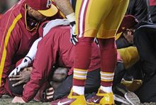Redskins quarterback Robert Griffin III lies injured on the field Sunday during the fourth quarter after a game-ending knee injury in the loss to Seattle. (Preston Keres/Special to The Washington Times)