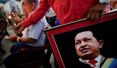 A Venezuelan Embassy worker at a monthly service for the sick at a Catholic church in Regla, Cuba, shows support for Hugo Chavez, his country's ailing president hospitalized in Havana and unable to attend his inauguration Thursday. (Associated Press)