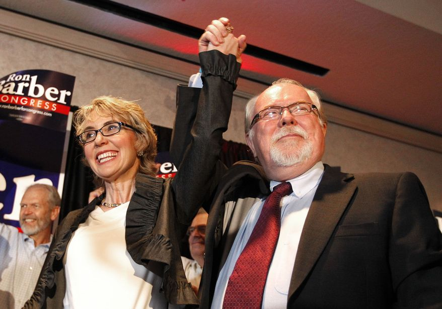 **FILE** Democratic candidate Ron Barber (right), who won an election to fill former Arizona Rep. Gabrielle Giffords' congressional seat, celebrates the victory on June 12, 2012, with Giffords and supporters at a post-election event, in Tucson, Ariz. (Associated Press)