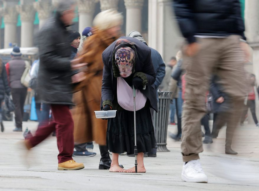 A woman begs for money amid passers-by in Milan, Italy, amid tough times. The number of jobless people in the 17 European Union countries that use the euro rose to 18.8 million, the highest figure since the single currency was founded in 1999. (Associated Press)