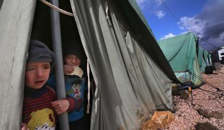 Syrian refugee boys look Jan. 7, 2013, outside their tent at a temporary refugee camp in the eastern Lebanese town of Marj near the border with Syria. (Associated Press/File)