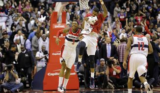 Washington Wizards guard Bradley Beal (3) and forward Trevor Ariza, center, celebrate Beal's game winning shot in the second half of an NBA basketball game against the Oklahoma City Thunder Monday, Jan. 7, 2013, in Washington. The Wizards won 101-99.(AP Photo/Alex Brandon)