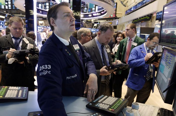 Specialist Patrick King (second from left) works on the floor of the New York Stock Exchange on Jan. 8, 2013. (Associated Press)