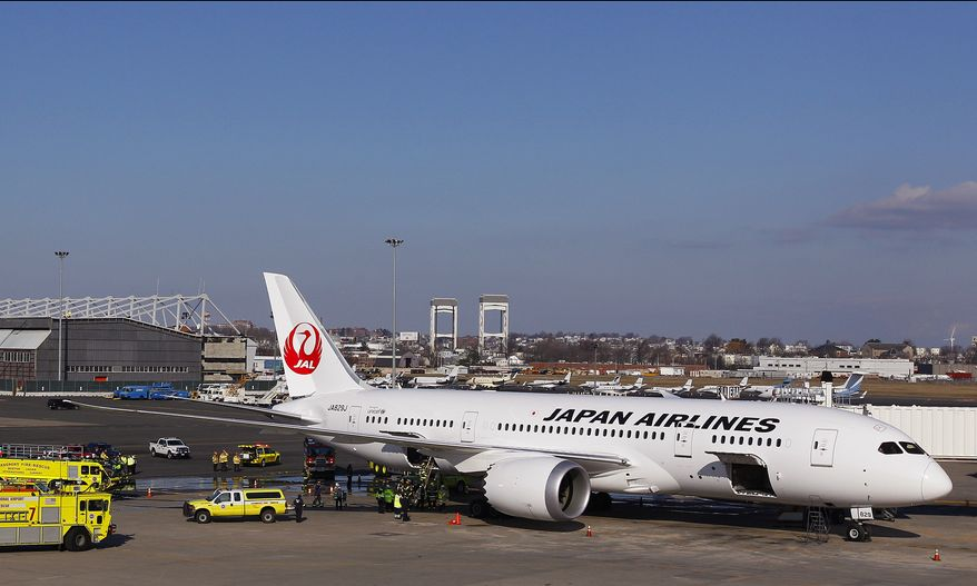 """A Japan Airlines Boeing 787 """"Dreamliner"""" jet aircraft is surrounded by emergency vehicles while parked at a Terminal E gate at Logan International Airport in Boston on Monday, Jan. 7, 2013, following a fire that started in one of the plane's lithium ion batteries. (AP Photo/Stephan Savoia)"""