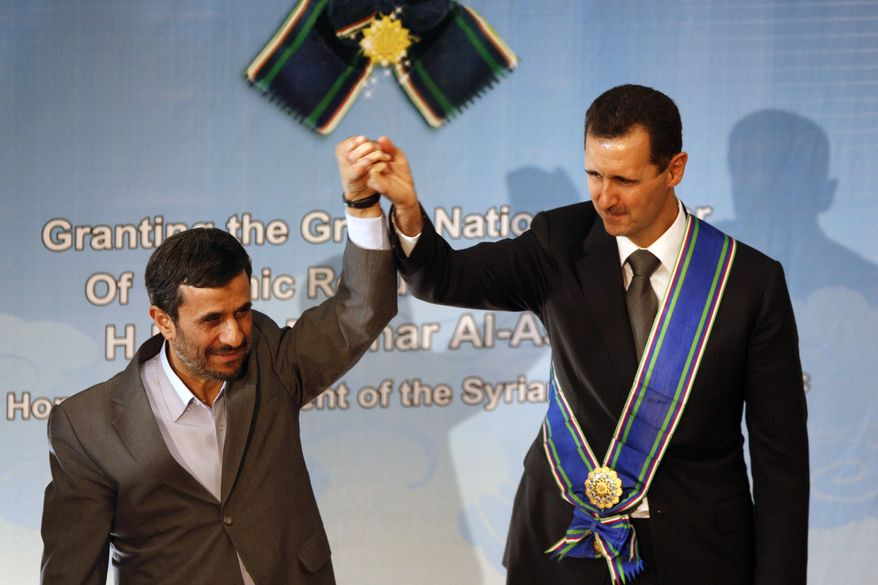 ** FILE ** In this Oct. 2, 2010, file photo, Iranian President Mahmoud Ahmadinejad, left, holds up the hand of his Syrian counterpart Bashar Assad after he awarded Iran's highest national medal to Assad, in a ceremony in Tehran, Iran. (AP Photo/Vahid Salemi, File)