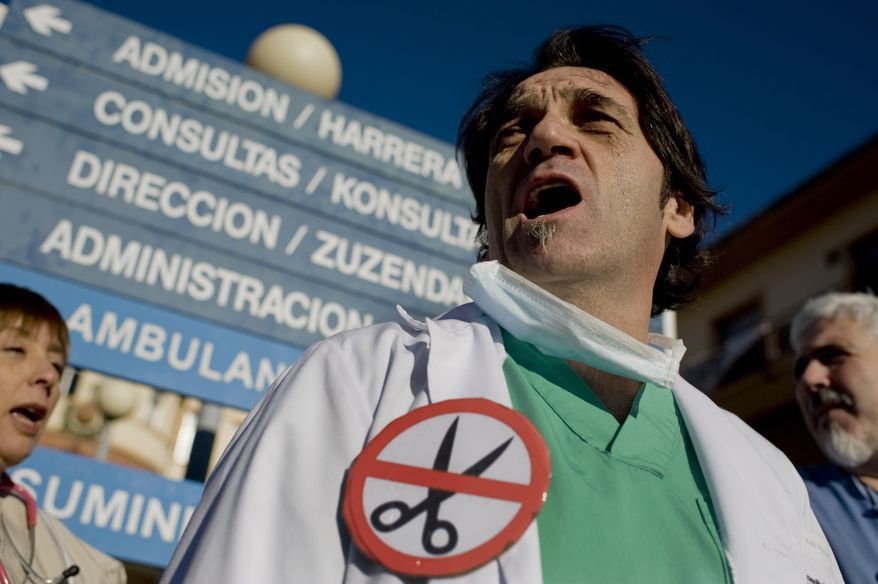 **FILE** Health workers protest outside a hospital in Pamplona, Spain, on Jan. 8, 2013, against austerity measures. Spain Treasury says it plans to borrow some euro 230 billion ($300 billion) in 2013, down from euro 250 billion last year, and expects a more relaxed year in interest rates compared to 2012 when it came close to seeking a sovereign bailout. (Associated Press)