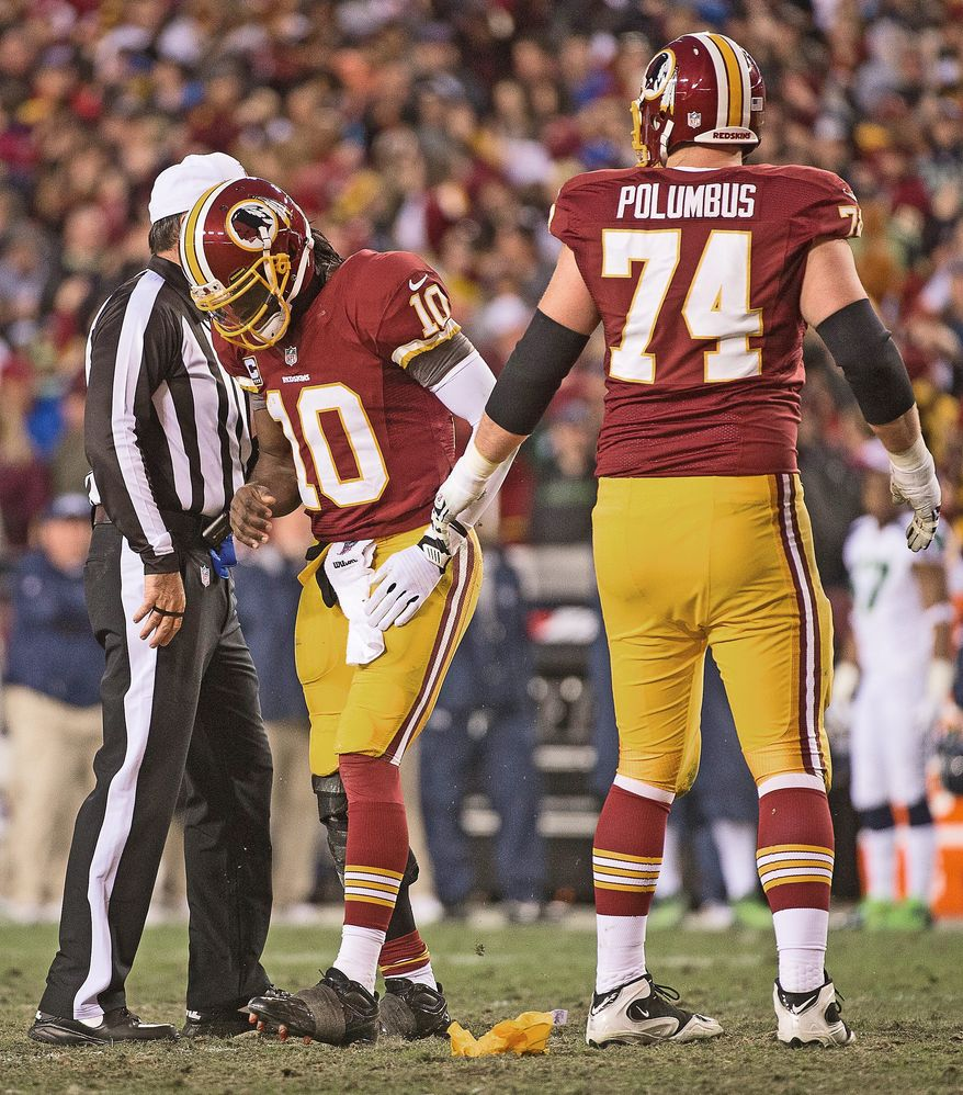 Redskins tackle Tyler Polumbus (74) helps a hobbled Robert Griffin III after the quarterback was shaken up on an illegal hit in the first quarter. Griffin had first aggravated his injured right knee two plays earlier on a rollout. (Andrew Harnik/The Washington Times)