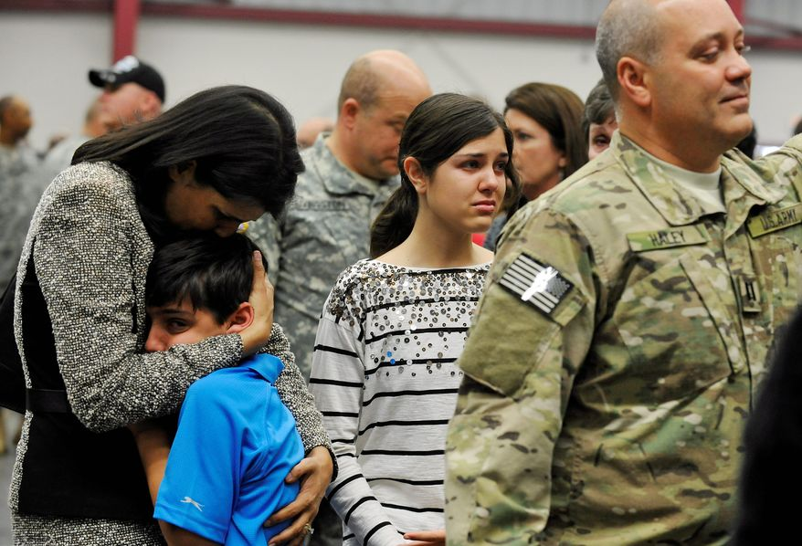 South Carolina Gov. Nikki Haley comforts her 10-year-old son, Nalin, and 14-year-old daughter, Rena, at a National Guard site outside Columbia where her husband, Michael, was preparing to depart with a Guard unit. Capt. Michael Haley will take part in a month of training before his deployment to Afghanistan to work with locals to improve farming practices. (Associated Press)
