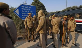 Policemen report for duty at a district court, where the accused in a gang rape are to be produced for trial, in New Delhi, India, Thursday, Jan. 10, 2013. Police have badly beaten the five suspects in the brutal rape and killing of the young woman on a New Delhi bus, the lawyer for three of the men said Thursday, accusing authorities of tampering with evidence in the case that has transfixed India. (AP Photo/Saurabh Das)