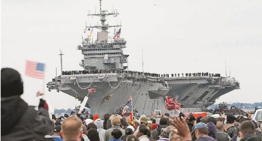 ** FILE ** Family members and friends in Norfolk, Va., welcome home the USS Enterprise after its 25th and final deployment, along with the 5,500 sailors and Marines who spent nearly eight months at sea. The Enterprise is the world's first nuclear-powered aircraft carrier. (Associated Press)