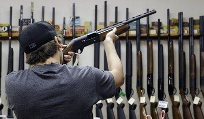 **FILE** A customer checks out a shotgun at Burdett & Son Outdoor Adventure Shop in College Station, Texas, on Dec. 19, 2012. (Associated Press)