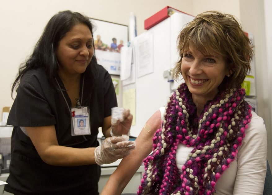 **FILE** Diane Ewell of Phoenix (right) gets a flu shot from nurse Bhagwati Bhakta at Mollen Immunization Clinics in Scottsdale, Ariz., on Jan. 10, 2013. Arizona health officials say flu activity is widespread in the state this week with influenza reported in 14 of its 15 counties. (Associated Press/The Arizona Republic)