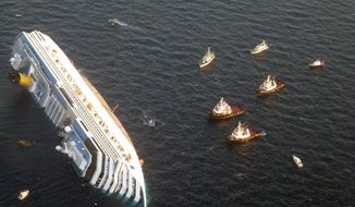 **FILE** The luxury cruise ship Costa Concordia leans on its side after running aground the tiny Tuscan island of Giglio, Italy, on Jan. 14, 2012. (Associated Press/Guardia di Finanza)