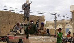 ** FILE ** Fighters from the Islamist group Ansar Dine stand guard in Timbuktu, Mali, on Friday, Aug. 31, 2012, as they prepare to publicly lash a member of the Islamic Police found guilty of adultery. (Associated Press)