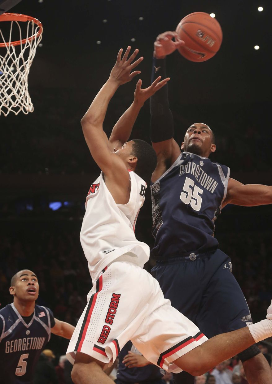 Georgetown's Jabril Trawick (55) blocks a shot by St. John's Jamal Branch during the second half of an NCAA college basketball game, Saturday, Jan. 12, 2013, at Madison Square Garden in New York. Georgetown won 67-51. (AP Photo/Mary Altaffer)