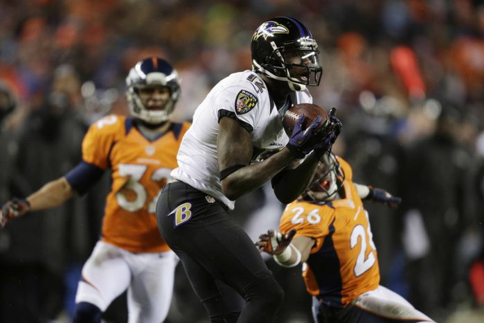 Baltimore Ravens wide receiver Jacoby Jones (12) catches a touchdown pass as Denver Broncos free safety Rahim Moore (26) and Denver Broncos defensive back Tony Carter (32) defend in the fourth quarter o