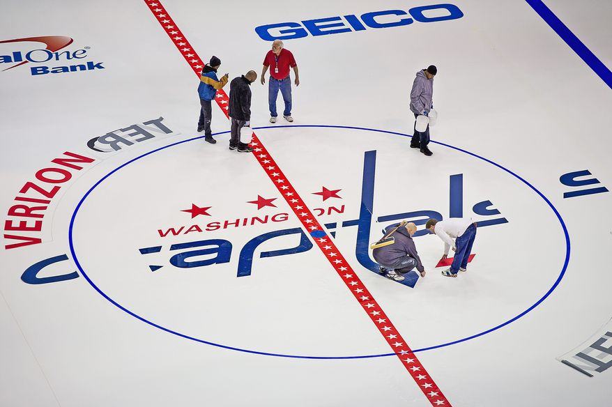 Workers with the Verizon Center put down the markings and logos on the ice surface for the Washington Capitals ice rink on Jan. 9, 2013. The shortened, 48-game season begins for the Capitals on Jan. 19 against division foe Tampa Bay. (Andrew Harnik/The Washington Times)