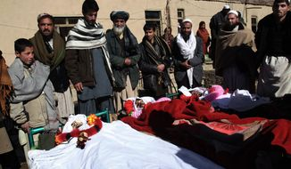 Villagers stand near the bodies of men killed in an explosion in Sayedabad, in Afghanistan's Wardak province, southwest of Kabul on Sunday, Jan. 13, 2013. The explosion killed seven Afghan villagers as they tried to pull bodies of insurgents killed from the rubble of a village mosque after a night raid by NATO and Afghan troops in the country's east, officials said. Four insurgents and an Afghan soldier also were reported to have been killed. (AP Photo/Rahmatullah Nikzad)