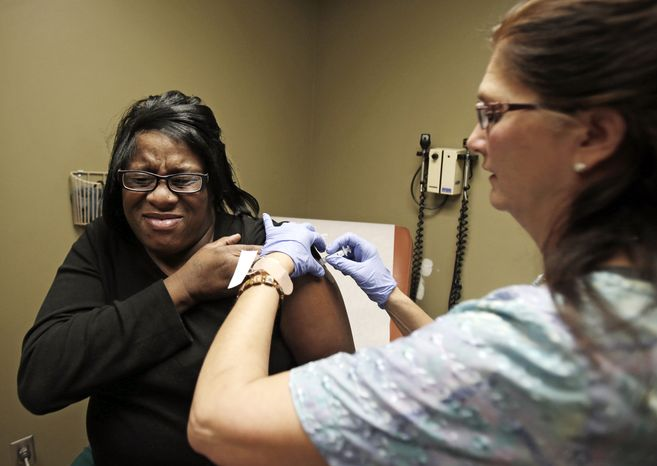 Nurse Debbie Smerk (right) administers a flu shot to Pamela Black at MetroHealth in Cleveland on Thursday, Jan. 10, 2013. (AP Photo/Tony Dejak)