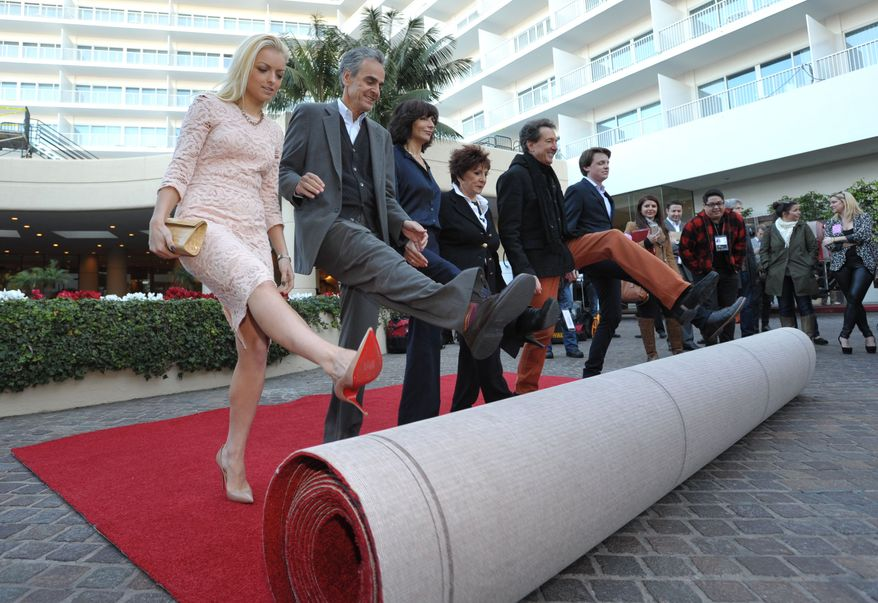 Miss Golden Globe Francesca Eastwood (from left), Dick Clark Productions CEO Allen Shapiro, Dick Clark Productions President Orly Adelson, HFPA President Aida Takla-O'Reilly, producer Barry Adelman and Mr. Golden Globe Sam Michael Fox roll out the red carpet at the Golden Globe Awards preview day at the Beverly Hilton Hotel on Friday, Jan. 11, 2013, in Beverly Hills, Calif. (John Shearer/Invision/AP)