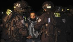 """Israeli border police evict a Palestinian activist from an area known as E-1 near Jerusalem on Sunday, Jan. 13, 2013. Palestinian activists erected tents in the area on Friday, saying they wanted to """"establish facts on the ground"""" to stop Israeli construction in the West Bank. (AP Photo/Nasser Shiyoukhi)"""