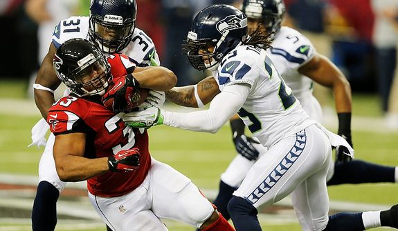Atlanta Falcons running back Michael Turner (33) his hit by Seattle Seahawks free safety Earl Thomas (29) and Seattle Seahawks strong safety Kam Chancellor (31) during the first half of an NFC divisional playoff NFL football game Sunday, Jan. 13, 2013, in Atlanta. (AP Photo/John Bazemore)