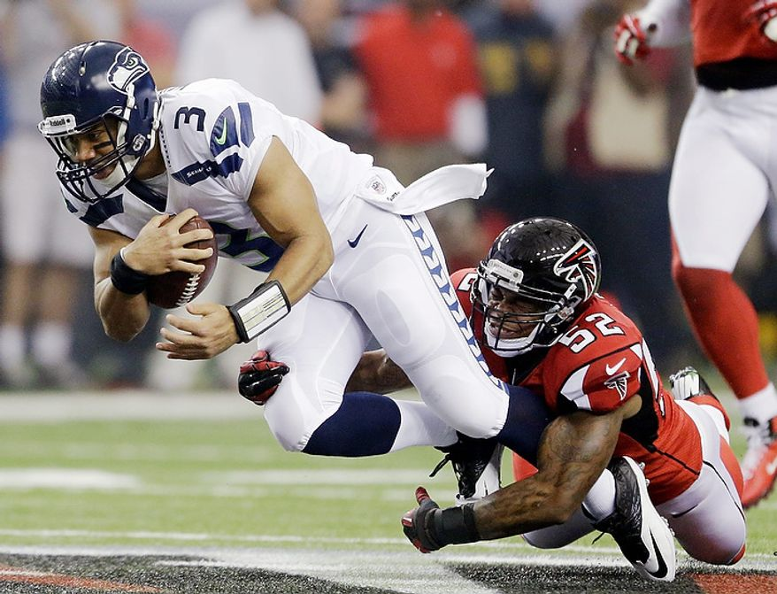 Seattle Seahawks quarterback Russell Wilson (3) is tackled by Atlanta Falcons' Akeem Dent (52) during the first half of an NFC divisional playoff NFL football game Sunday, Jan. 13, 2013, in Atlanta. (AP Photo/David Goldman)