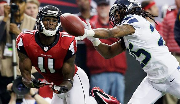 Atlanta Falcons wide receiver Julio Jones (11) misses a catch as Seattle Seahawks cornerback Richard Sherman (25) defends during the first half of an NFC divisional playoff NFL football game Sunday, Jan. 13, 2013, in Atlanta. (AP Photo/Dave Martin)