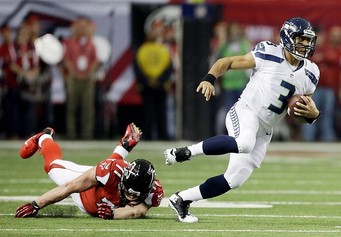 Seattle Seahawks quarterback Russell Wilson (3) runs past Atlanta Falcons defensive end Kroy Biermann (71) during the first half of an NFC divisional playoff NFL football game Sunday, Jan. 13, 2013, in Atlanta. (AP Photo/David Goldman)