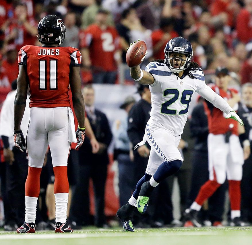 Seattle Seahawks free safety Earl Thomas (29) reacts to a turnover as Atlanta Falcons wide receiver Julio Jones (11) looks on during the second half of an NFC divisional playoff NFL football game Sunday, Jan. 13, 2013, in Atlanta. (AP Photo/David Goldman)