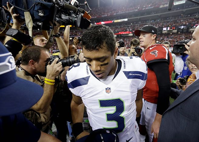 Seahawks quarterback Russell Wilson leaves the field after shaking hands with Atlanta Falcons quarterback Matt Ryan after an NFC divisional playoff NFL football game Sunday, Jan. 13, 2013, in Atlanta. The Falcons won 30-28. (AP Photo/David Goldman)