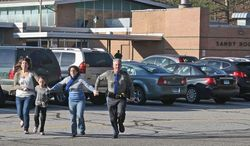 ** FILE ** A police officer leads two women and a child from Sandy Hook Elementary School in Newtown, Conn., on the day of the mass killings. (Newtown Bee via Associated Press)