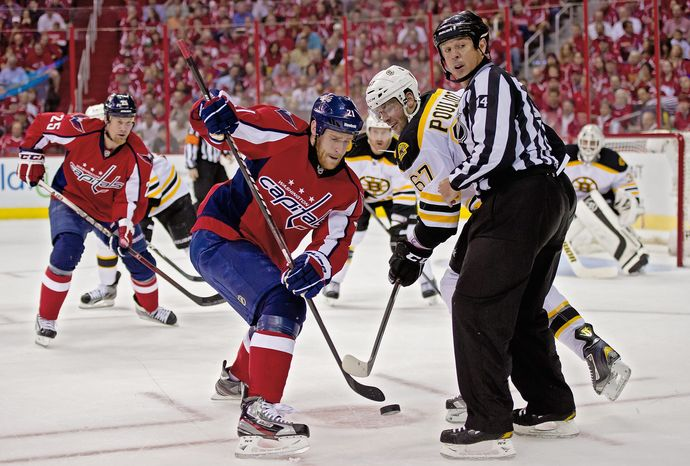 Capitals center Brooks Laich battles for the puck with Bruins left wing Benoit Pouliot during Game 3 of the opening-round playoff series last April. (Andrew Harnik/The Washington Times)